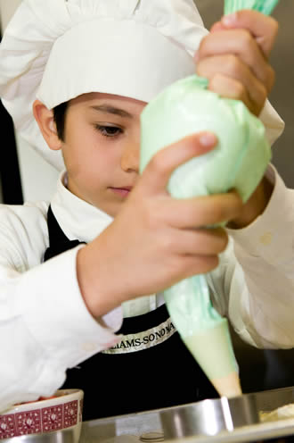 A boy chef pouring batter in to a pan.